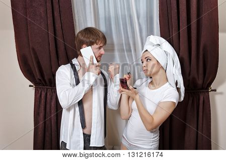 Morning couples. Husband and wife are going to work. Man talking on the phone and asks the girl to hurry. Girl doing make-up with a towel on her head.
