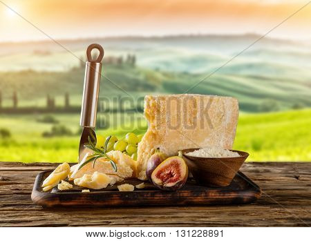 Parmesan cheese on cutting board placed on wood, blur countryside on background