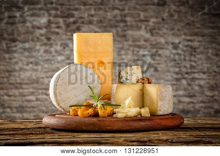 Various types of cheese placed on wooden table, copyspace for text. brick wall on background