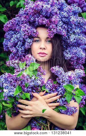 Portrait of a beautiful young girl in a wreath of lilac.