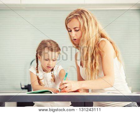 Parent teaches a child to write. Mom helping her daughter left-handed do homework