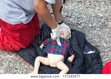 First aid training. Paramedic demonstrate Cardiopulmonary resuscitation (CPR) on infant CPR dummy. Child CPR dummy cardiac massage. poster