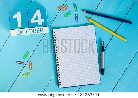 October 14th. Image of October 14 wooden color calendar on blue background. Autumn day. Empty space for text.