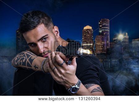 Portrait of handsome young tattooed man shots with gun against someone at night in city
