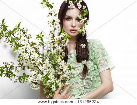 Beautiful brunette girl in green summer dress with a gentle romantic make-up pink lips holding flowers. The beauty of the face. Portrait shot in the studio. poster