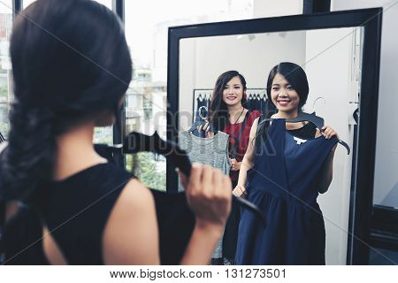 Young smiing woman with a dress looking at herself in mirror