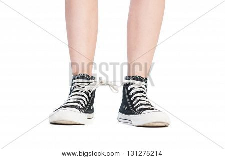 Shoelaces prank using teen sneakers on white background