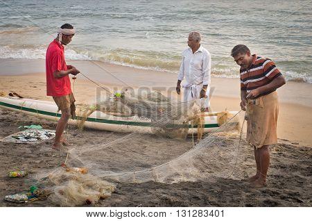 VARKALA INDIA - OCT 16 2014: Unidentified Indian Fishermen with fishing net on beach in Varkala. Kerala. India