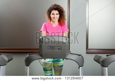 Beautiful Female Smiling And Exercising On Treadmill