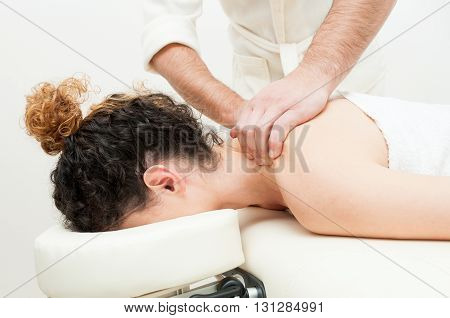 Young Woman Having Back Or Shoulders Massage In Spa Center