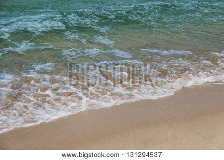 Gentle waves lap onto golden sands. St. Ives, Cornwall, England.