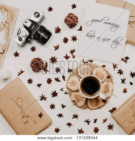 phrase Good morning have a nice day in calligraphy style on paper with coffee cup, wooden stand, star anise, presents and film camera at white background. Top view, flat lay