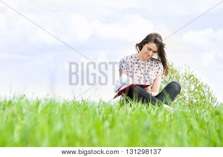 Young Smiling Woman Sitting On Meadow And Writing Something