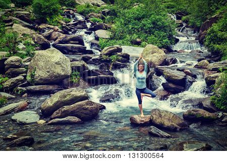 Vintage retro effect hipster style image of woman practices balance yoga asana Vrikshasana tree pose at waterfall outdoors. Himachal Pradesh, India. Panorama