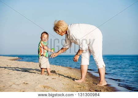 Happy baby with his grandmother in the summer. Grandmother holding a baby in her arms. Cheerful people grandmother with a baby in her arms.
