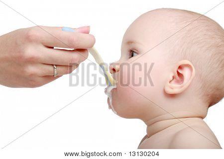Feeding. Beautiful baby. Shot in studio. Isolated on white.