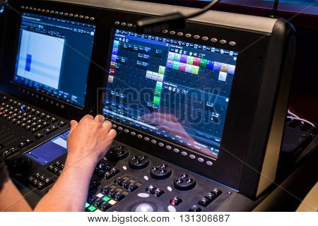 Large modern show light controller with lighted screen operators hand and ajusted presets