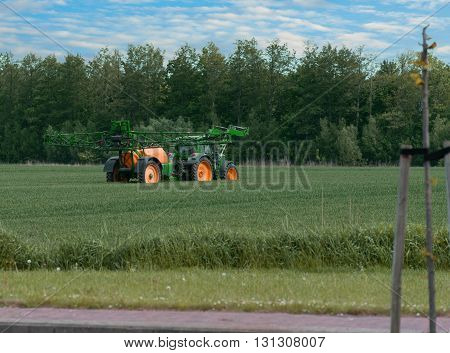 Tractor with sprayer during application of pesticides