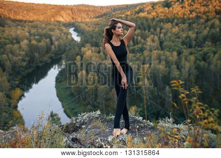 Full-length portrait of young girl doing yoga in the mountains