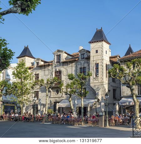 Saint Jean de Luz France - May 20 2016: People enjoying a bar terrace on Place Louis XIV of Saint-Jean de Luz with Maison Louis XIV in background. Aquitaine. France.