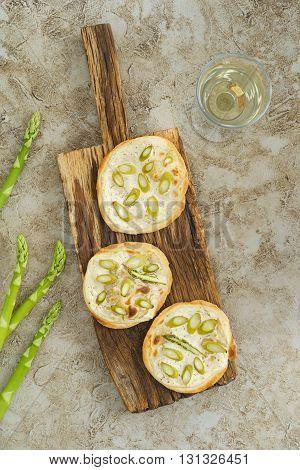 Three mini green asparagus tarte flambee on rustic wooden bards
