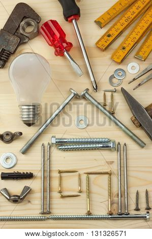Building a house for the family. Plans to build a small house. Architect designing a house for a young family. House from nails and screws. Needed for building. Ideas about building a house.