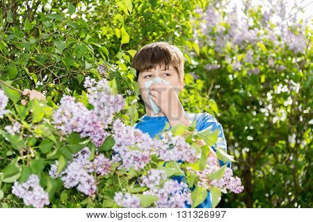 Teen boy with allergic rhinitis near blossoming lilac