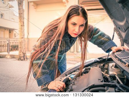 Woman with broken down car looking to engine - Young female driver and unexpected automobile breakdown along road trip - Concept of human stress in everyday life with dramatic tones and vignetting