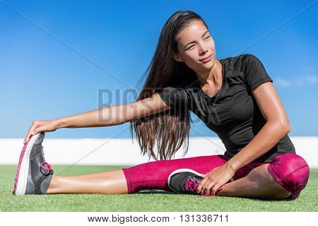 Fitness woman stretching one leg toe-touch stretch exercising hamstring and glute muscles stretches. Sporty Asian athlete exercising sitting forward bend legs exercise on grass in sunny outdoor gym.