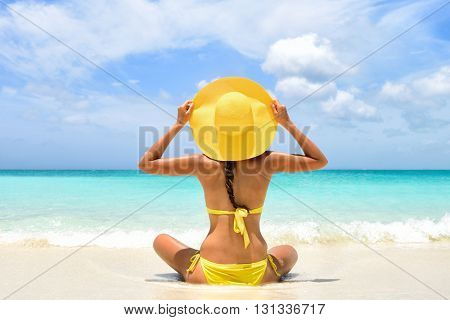 Happy carefree woman relaxing sitting in sand enjoying tropical beach destination. Perfect paradise summer vacation happiness. Back view of bikini girl holding yellow fashion hat on Caribbean holiday.