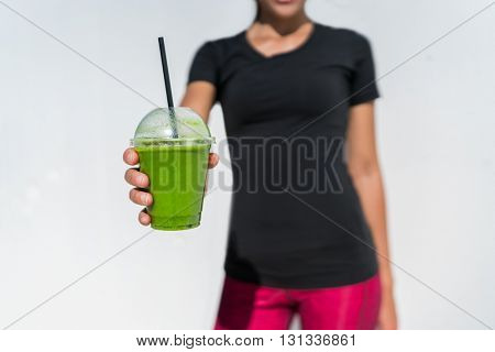 Healthy eating lifestyle fitness athlete woman drinking green smoothie cup for vegan weight loss diet. breakfast juicing trend. Person showing plastic container at outdoor cafe or juice bar.