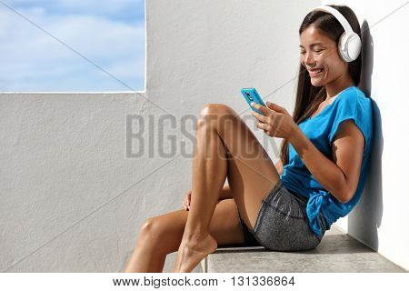 Asian healthy yoga woman listening to smartphone music with headphones relaxing outside on home summer terrace. Active living happy young girl enjoying fitness video or audio program on mobile phone.
