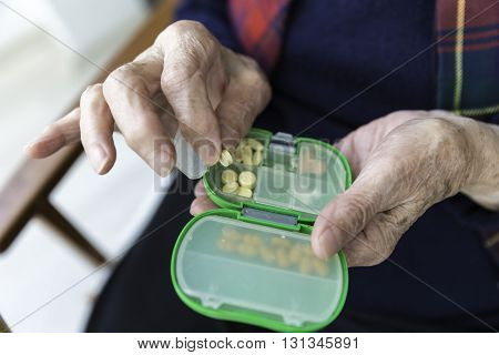 Elderly Turkish woman taking pills from green colored medicine box closeup view