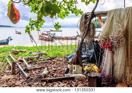 Rawai Thailand - October 27 2013: Fishing nets & tackle hang on Rawai beach & traditional long-tail boats moored off-shore on southern tip of Phuket southern Thailand