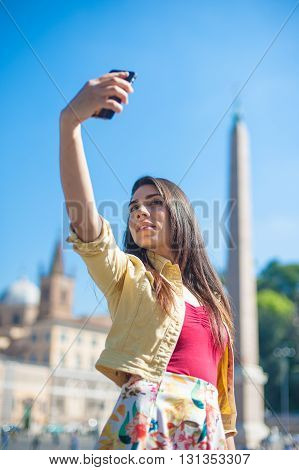 Young tourist woman taking selfie picture with mobile phone in Rome piazza del popolo