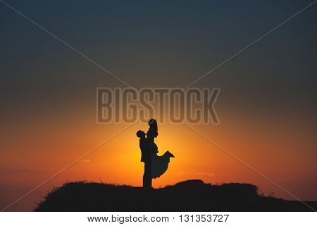 Silhouette of a loving couple on the background of the setting sun, mountains, islands and sea. Santorini. Greece. Just married. Walk. Walk at sunset. Walk through the mountains at sunset.