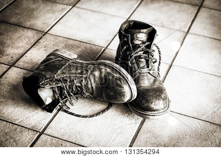 Black leather boots on a tiled floor. They lie there as if  their tired bearer had stripped them with great relief and happy to be now able to recover from the day's exertions.