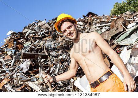 young worker in a junkyard shoveling iron scrap