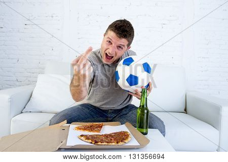 young man holding ball watching football game on television at home sofa couch with pizza box and beer bottle celebrating goal or victory gesturing crazy giving the finger to the opponent team