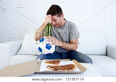young soccer supporter man holding ball and beer bottle watching football game on television sitting at home couch looking dejected sad and disappointed for failure or defeat