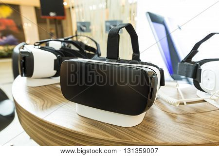 Sofia Bulgaria - May 13 2016: Virtual reality (VR) headsets (glasses) on a table. VR is immersive multimedia or computer-simulated reality - a computer technology that replicates an environment and simulates a user's physical presence and environment to a