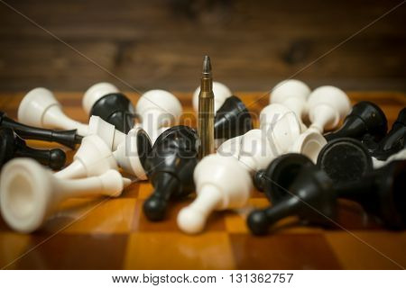 One riffle bullet on chessboard among lying chess pieces. Concept of military power
