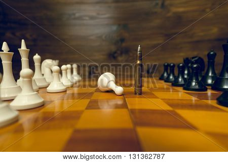 Closeup photo of bullet winning in chess game. Concept of power of guns