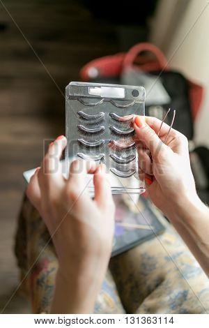 Closeup photo of stylist holding set of fake eyelashes