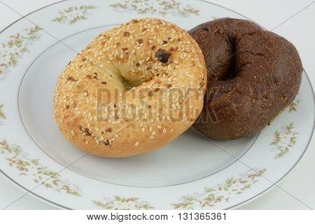 Onion sesame seed and pumpernickel bagel on plate