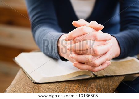 Female hands in a position for prayer over an open Bible.