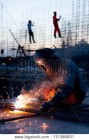 Welding and bright sparks on steel constructions. Hard job. Night time