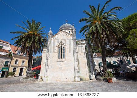 HERCEG NOVI MONTENEGRO - SEPTEMBER 13 2015: Unidentified tourists walk on the square Duke Stefan Bellavista near Orthodox Church of Archangel Michael in Herceg Novi Montenegro