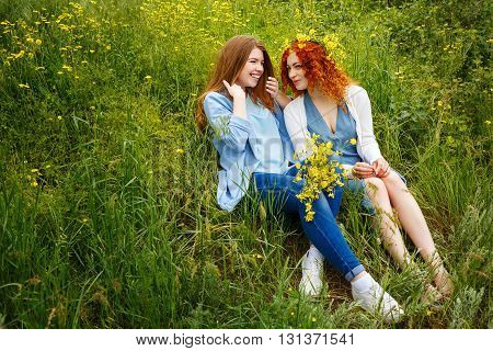 Best friends forever. Girlfriends talking in the park. BFF. A girl holding a bouquet of wildflowers. Gossip