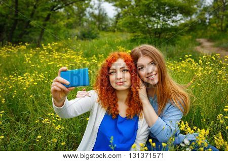 Best friends forever. Girlfriends doing selfie gentle on the phone in the park. BFF. Close friends. Gentle friendship.